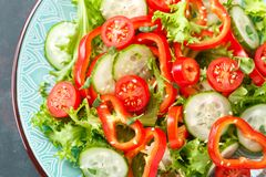 stock image of  healthy vegetarian vegetable salad of fresh lettuce, cucumber, sweet pepper and tomatoes. vegan plant-based food. flat lay