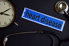 stock image of  heart disease on the print paper with healthcare concept inspiration. alarm clock, black stethoscope.