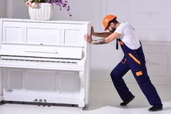 stock image of  heavy loads concept. loader moves piano instrument. courier delivers furniture, move out, relocation. man with beard