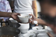 stock image of  help with feeding homeless people to alleviate hunger. poverty concept