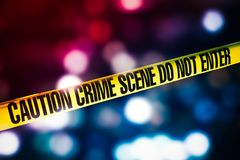 stock image of  crime scene tape with red and blue lights on the background