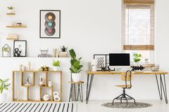 stock image of  hipster, white home office interior with natural, wooden furniture, industrial elements, green plants and a computer on a big desk