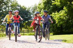 stock image of  hispanic family on cycle ride in countryside