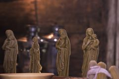 stock image of  hobbies and creativity, craft. faith and religion, christianity. candle figures of saints from beeswax made by hands in dim light