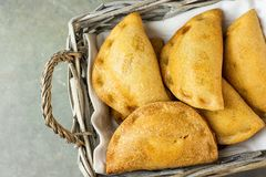 stock image of  home baked empanadas turnover pies with pisto vegetable cheese filling in tomato sauce in wicker basket. spanish pastry dark table