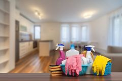 stock image of  home cleaning service concept with supplies. close up of cleaning supplies in front of livingroom.