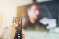 stock image of  home entertainment. hand hold smart tv remote control with a television blur background