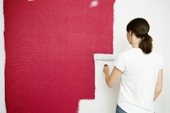 stock image of  home improvement. beautiful woman painting wall with paint roller.