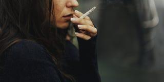 stock image of  homeless adult woman smoking cigarette addiction