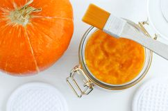 stock image of  homemade pumpkin face mask in a glass jar. diy cosmetics and spa. top view, copy space.