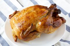stock image of  homemade tasty rotisserie chicken on white plate, side view. close-up
