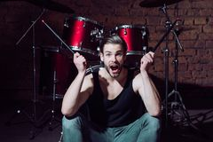 stock image of  i beat things for a living. excited man on stage at percussion instrument. enjoying instrumental music. man drummer with