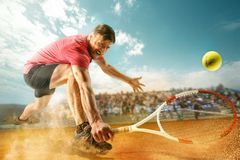 stock image of  the one jumping player, caucasian fit man, playing tennis on the earthen court with spectators