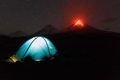 stock image of  illuminated tourist tent at night on background erupting volcano