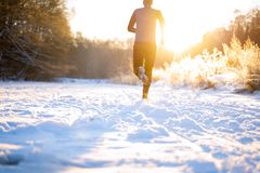 stock image of  image from back of man in sportswear, red cap on run in winter