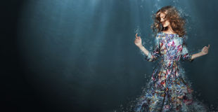 stock image of  immersion. woman in deep blue sea. fantasy