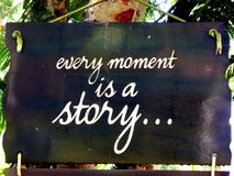 stock image of  inspirational motivation quote every moment is a story on a sigh hanging in tree