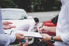 stock image of  insurance agent examine damaged car and customer filing signature on report claim form process after accident, traffic accident