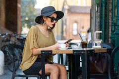 stock image of  elegant italian woman with hat and glasses writes a message with her smartphone