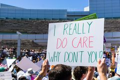 stock image of  `i really do care why don`t you` sign raised at the `families belong together` rally