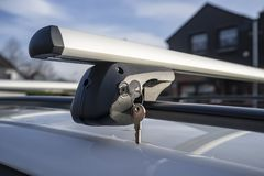 stock image of  keys in the lock fasten the holder for the car trunk or cargo box to the vehicle roof, on a sunny spring day against the blue sky