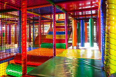 stock image of  kids running inside a colorful indoor playground
