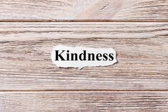 stock image of  kindness of the word on paper. concept. words of kindness on a wooden background
