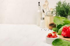 stock image of  kitchen white interior with raw fresh green salad, red cherry tomatoes, kitchenware on soft white wood table, copy space.