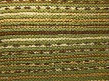 stock image of  knitted fabric texture. background image. hobbies, leisure, crafts. horizontal arrangement of the pattern. green and brown