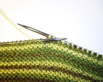 stock image of  knitting. knitted fabric and knitting needles. work process. hobbies leisure crafts