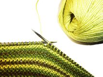 stock image of  knitting. knitted fabric, knitting needles and a skein of yarn. work process. hobbies leisure crafts