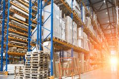 stock image of  large logistics hangar warehouse with lots shelves or racks with pallets of goods and sunlight effect