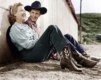 stock image of  laughing couple in western attire sitting on the ground