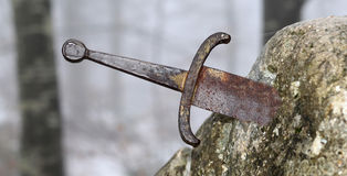 stock image of  legendary excalibur sword into the stone in the middle of the fo