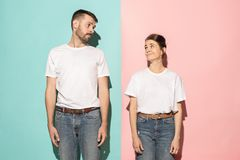 stock image of  let me think. doubtful pensive couple with thoughtful expression making choice against pink background