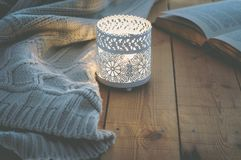 stock image of  lit candle white knitted sweater open book on plank wood table by window. cozy winter autumn evening. natural light
