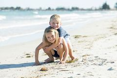 stock image of  little adorable and sweet siblings playing together in sand beach with small brother hugging his beautiful blond young sister enjo