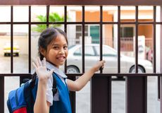 stock image of  little asian girl in uniform say good bye before leaving to school in the morning with blue back pack