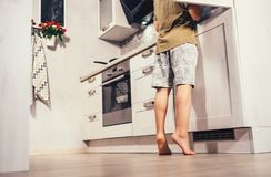 stock image of  little boy on kitchen try to find something in rifregerator