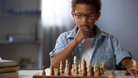 stock image of  little boy thinking on chess move, intelligent hobby, logic development, leisure