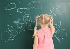 stock image of  little child drawing family with white chalk