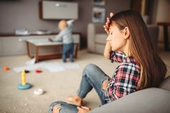 stock image of  little child playing in room, mother in stress