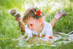 stock image of  little girl reading tales lying in green grass
