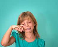 stock image of  little girl with sad expression and tears. crying child on turquoise background. emotions.