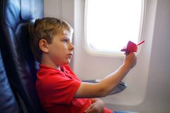 stock image of  little kid boy playing with red paper plane during flight on airplane. child sitting inside aircraft by a window. family