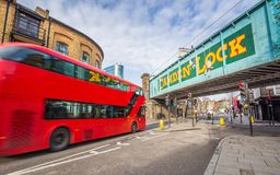 stock image of  london, england - iconic red double decker bus on the move at the world famous stables market of camden town