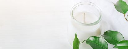 stock image of  long banner for organic cosmetics wellness white candle in glass jar fresh tree branches with green leaves on wood background. spa