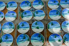 stock image of  a lot of wooden souvenirs with landscapes of maldives on it