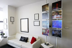 stock image of  lounge room with white couch and lcd displays