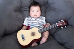 stock image of  lovely baby sitting on the soft sofa with mini guitar. babies musician. practice music skills for children. music and kids.